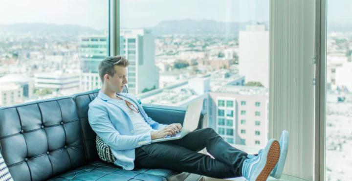 窓のそばでラップトップで作業する男性